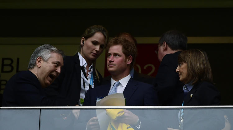 Prince Harry (centre) holds a Brazil jersey as he waits for the start of the match between Brazil and Cameroon at the Mane Garrincha National Stadium in Brasilia on June 23, 2014