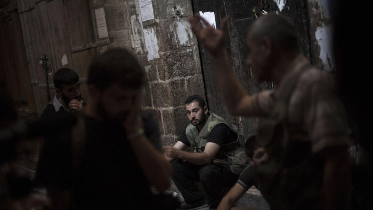 In this Saturday, Sept. 22, 2012 photo, Free Syrian Army fighters take a rest in the old city area of Aleppo, Syria. (AP Photo/ Manu Brabo)