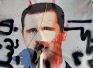 A slipper hangs on a vandalised poster of Syrian President Bashar al-Assad lying in a trash container in the northern city of Aleppo. A commercial hub and home to 2.5 million people, Syria&#39;s second city Aleppo has become a new front in the country&#39;s 16-month uprising, after being largely excluded from the violence