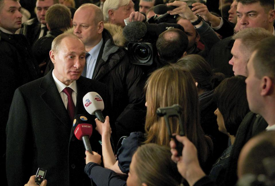 Russian Prime Minister and presidential candidate Vladimir Putin, left, talks to the media at a polling station in Moscow, Sunday, March 4, 2012. Polling stations have opened across Russia's vast expanse for the presidential election widely expected to return Vladimir Putin to the Kremlin. (AP Photo/Ivan Sekretarev)