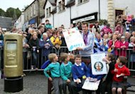 Scottish tennis player Andy Murray (C) poses with local children next to Royal Mail golden post box in the centre of Dunblane, Scotland. Murray, the first British man to win a Grand Slam title in 76 years, received a rapturous welcome in his Scottish home town on Sunday, but admitted that his golden summer was giving him nightmares