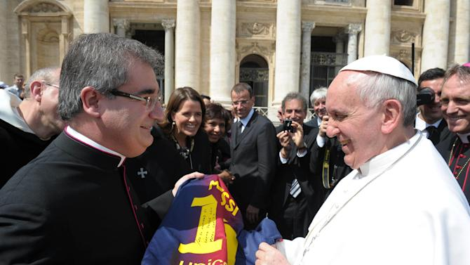 In this photo provided by the Vatican paper L'Osservatore Romano and made available Thursday, April 18, 2013, Mons. Miguel Delgado Galindo, left, presents a jersey of Argentine soccer star Lionel Messi to Pope Francis, at the Vatican Wednesday, April 17, 2013. (AP Photo/L'Osservatore Romano, ho)