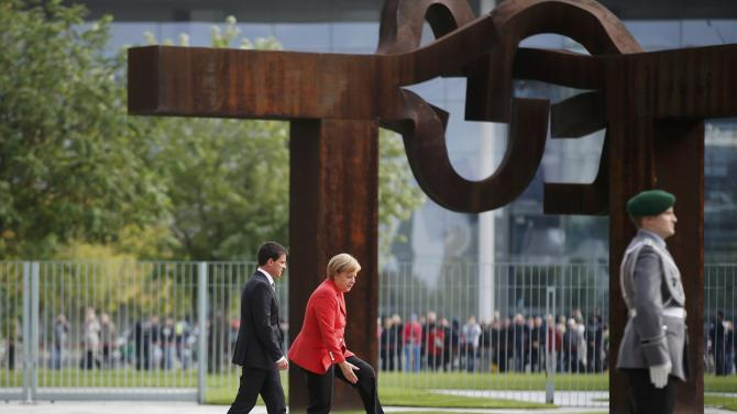 French Prime Minister Valls and German Chancellor Merkel review a guard of honour during a welcome ceremony at the Chancellery in in Berlin