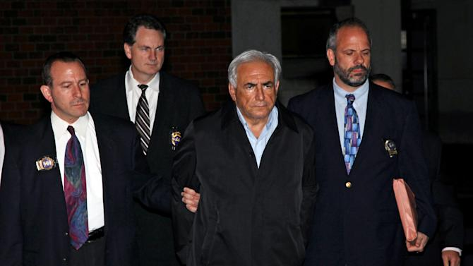 Dominique Strauss-Kahn, head of the International Monetary Fund, is lead from a police station Sunday, May 15, 2011 in New York where he was being held. The arraignment for Strauss-Kahn, who's accused of sexually assaulting a New York hotel maid, has been delayed. Strauss-Kahn's lawyer says his client agreed to an examination requested by prosecutors to obtain evidence in the case. His lawyer says an arraignment set for Sunday night will now happen Monday. Police arrested Strauss-Kahn early Sunday on charges including attempted rape. (AP Photo/Craig Ruttle)