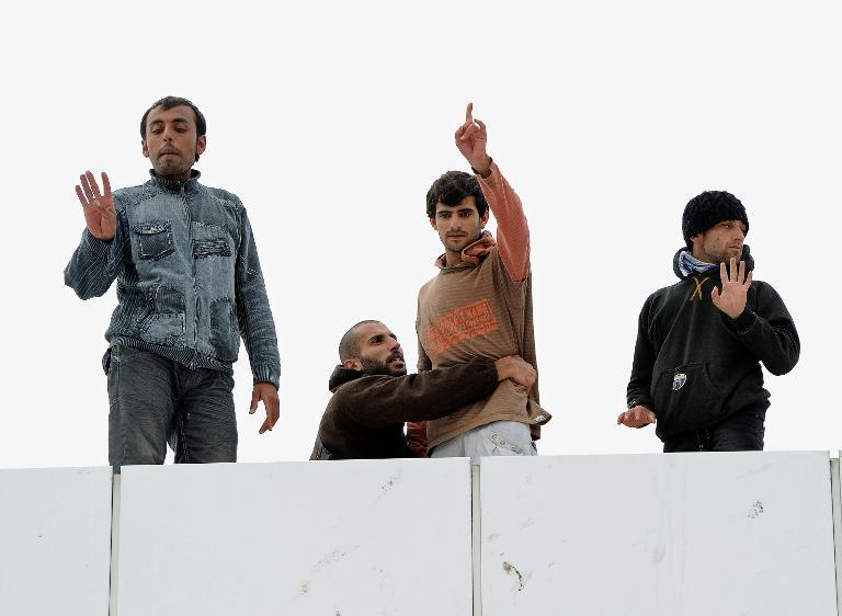 A Syrian refugee retains another one from jumping from the top of a building as they protest at the ferry terminal in Calais, northern France on October 4, 2013