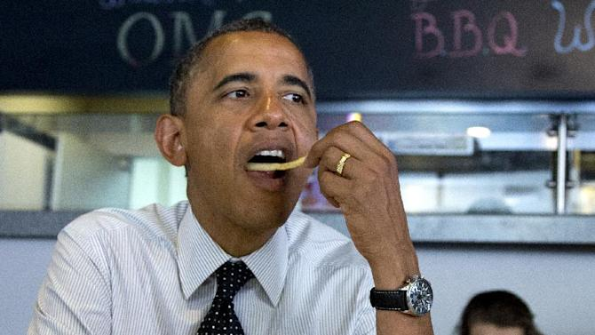 President Barack Obama pops a french fry into his mouth as he visits with students at OMG! Burgers, Thursday, Sept. 20, 2012, in Miami, Fla.  (AP Photo/Carolyn Kaster)