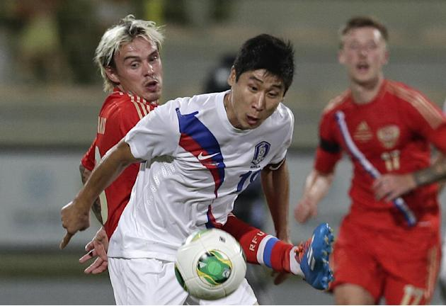 Russia's defender Andrey Yeshchenko, left, and South Korea's Keunho Lee compete for the ball during the international friendly soccer match between Russia and South Korea, in Dubai, United Arab Emirat