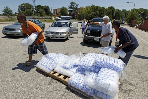 City workers George Kirk, right, and Joe Lane give away free bags of ice to residents at the Northwood Plaza shopping center in Baltimore on Monday July 2, 2012. Around 2 million customers from North Carolina to New Jersey and as far west as Illinois were without power Monday morning after a round of summer storms. (AP Photo/Jose Luis Magana)