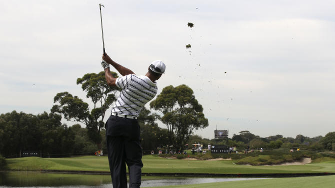 U.S. golfer Tiger Woods plays a shot across a water hazard on the 14th during a pro-am event of the Australian Open golf tournament in Sydney, Australia, Wednesday, Nov. 9, 2011. (AP Photo/Rob Griffith)