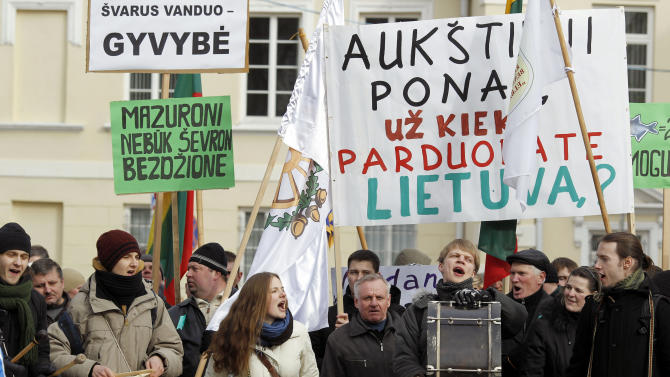 """CORRECT SPELLING OF CHEVRON Lithuanians gather for an anti-American demonstration rally at the President  palace, in Vilnius, Lithuania,Tuesday, Feb. 26, 2013. Protesters oppose government plans to explore shale gas fields in western part of the country. The main placard reads - """"How much for Lithuania, misters? Poster at left reads - """"Chevron - out"""". (AP Photo/Mindaugas Kulbis)"""