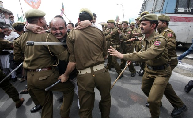 An activist from India's main opposition BJP scuffles with police during a protest in Jammu