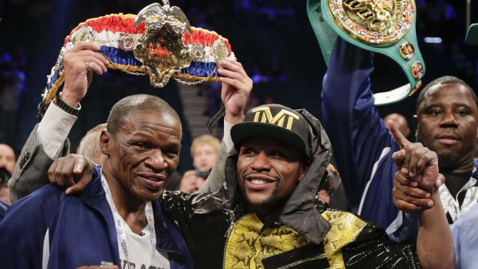 Floyd Mayweather Jr., right, poses for photos with his father, Floyd Mayeather Sr. after defeating Robert Guerrero by unanimous decision in a WBC welterweight title fight, Saturday, May 4, 2013, in Las Vegas. (AP Photo/Rick Bowmer)