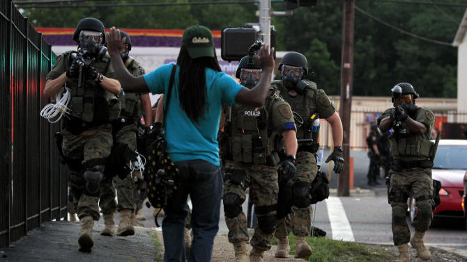 FILE - In this Aug. 11, 2014, file photo, police wearing riot gear walk toward a man with his hands raised Monday, Aug. 11, 2014, in Ferguson, Mo. On Aug. 9, a white police officer fatally shot Michael Brown, an unarmed black 18-year old, in the St. Louis suburb. (AP Photo/Jeff Roberson, File)