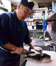 Japanese chef Shigekazu Suzuki cuts and trims a pufferfish to remove toxic internal organs at his restaurant Torafugu-tei in Tokyo. Suzuki is one of an exclusive coterie of Tokyo chefs who have undergone special training and licensing that allows them to serve the potentially fatal fish