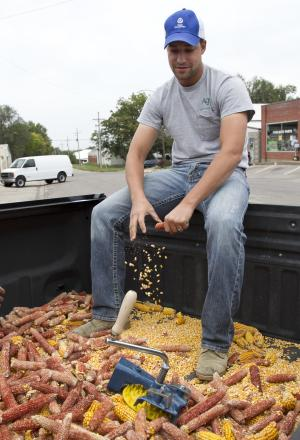 This Monday, Sept. 24, 2012 photo shows Nebraska fan Eric Otte shelling corn in the back of his pickup truck in Wahoo, Neb. Otte is waiting for the outcome of this year to decide whether he's on board with coach Bo Pelini. Otte thinks there is no reason why Nebraska fans shouldn't expect the Huskers to be in contention for conference and national championships every year. (AP Photo/Nati Harnik)
