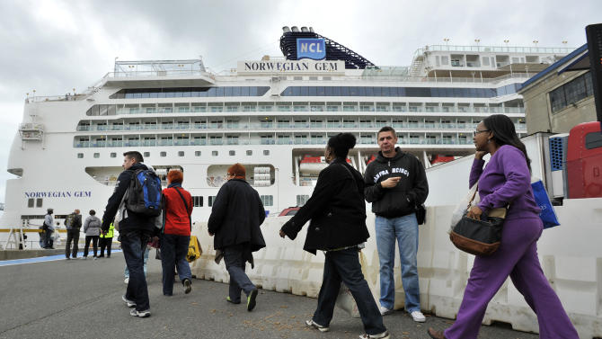 Passengers walk towards the Black Falcon Cruise Terminal in Boston, Wednesday, Oct. 31, 2012, where three of the New York bound cruise ships which were diverted after superstorm Sandy were docked. Sandy, the storm that made landfall Monday, caused multiple fatalities, halted mass transit and cut power to more than 6 million homes and businesses. (AP Photo/Josh Reynolds)