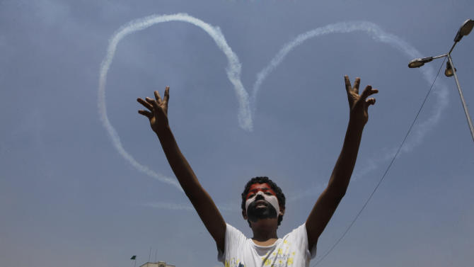 An Egyptian protester flashes v signs for military aircrafts forming a heart shape trails in the sky over Tahrir Square in Cairo, Egypt, Friday, July 5, 2013. Egypt's Muslim Brotherhood called for a wave of protests Friday, furious over the military's ouster of its president and arrest of its revered leader and other top figures, underlining the touchy issue of what role the fundamentalist Islamist movement might play in the new regime. (AP Photo/Amr Nabil)