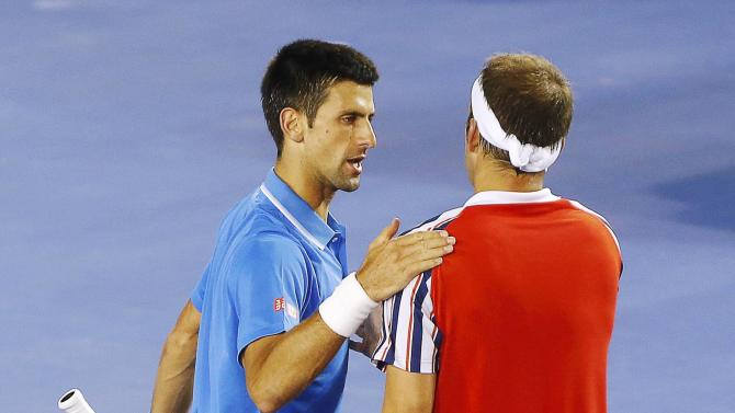 Djokovic of Serbia pats Muller of Luxembourg on the back after winning their men's singles match at the Australian Open 2015 tennis tournament in Melbourne