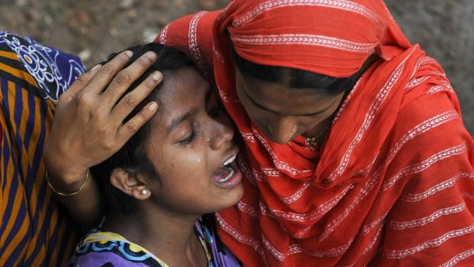 A Bangladeshi woman cries after identifying the body of her father at a makeshift morgue near the site of a building collapse in Savar, near Dhaka, Bangladesh, Tuesday, May 7, 2013. Hundreds of survivors of last month's collapse of a building housing garment factories in Bangladesh protested for compensation Tuesday, as the death toll from the country's worst-ever industrial disaster passed 700. (AP Photo/Ismail Ferdous)