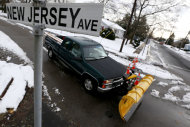 A snow plower drives on New Jersey Avenue as snow covered debris from Superstorm Sandy lies on the sidewalk, Thursday, Nov. 8, 2012, in Point Pleasant, N.J. A nor&#39;easter hit the New Jersey shore on Wednesday, pounding the region which was already hit by Superstorm Sandy. (AP Photo/Julio Cortez)