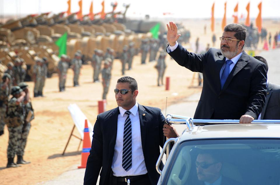 In this image released by the Egyptian Presidency, Egyptian President Mohammed Morsi, waves toward soldiers at a military base in Ismailia, Egypt, Wednesday, Oct. 10, 2012. (AP Photo/Egyptian Presidency)