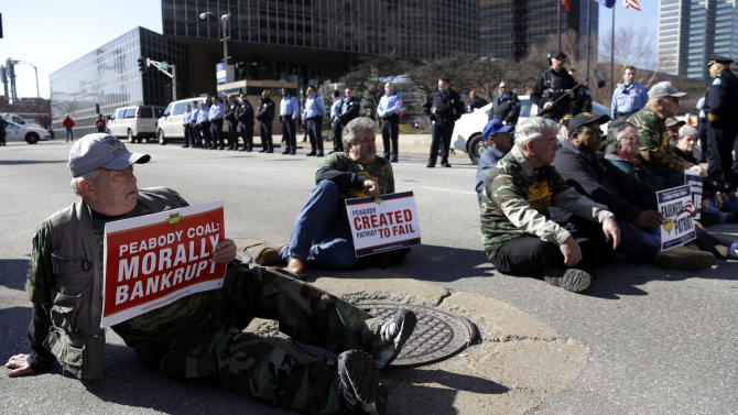 Kenny Smith, left, sits in the middle of a street with other members of the United Mine Workers of America as they wait to be arrested by police during a protest outside the of headquarters of Peabody Energy, one of the companies the union accuses of orchestrating business deals that bankrupted Patriot Coal, Wednesday, Feb. 13, 2013, in St. Louis. Ten people were arrested during the protest of bankruptcy proceedings that the union says jeopardizes pension and health care benefits for some 20,000 retirees and dependents. (AP Photo/Jeff Roberson)