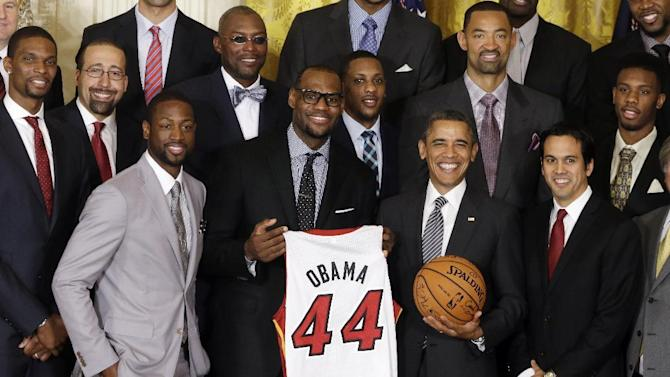 President Barack Obama stands with LeBron James, fifth from left, Dwayne Wade, third left, and coach Erik Spoelstra, right, as he honors the NBA champions Miami Heat basketball team in the East Room at the White House in Washington, Monday, Jan. 28, 2013. (AP Photo/Charles Dharapak)