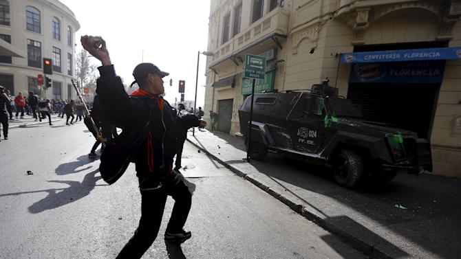 A demonstrator prepares to throw a store against a riot police vehicle during a demonstration