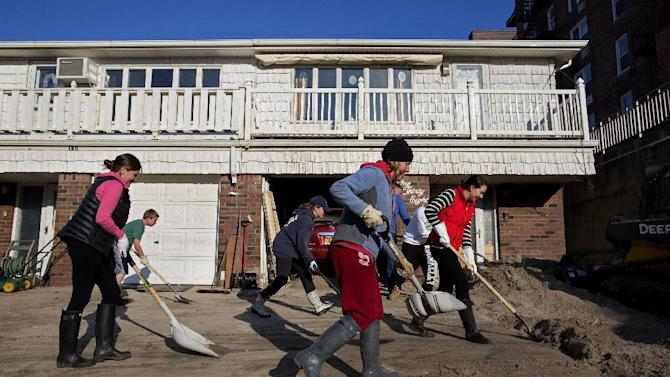 Neighbors volunteering to help another neighbor in need move deep sand from the house on Beach 121 Street in the Rockaway Park neighborhood of the borough of Queens, New York, Sunday, Nov. 11, 2012, in the wake of Superstorm Sandy. (AP Photo/Craig Ruttle)