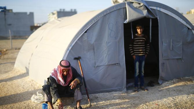 A Kurdish refugee man from the Syrian town of Kobani sits in front of a tent in a camp in the southeastern town of Suruc, Sanliurfa province