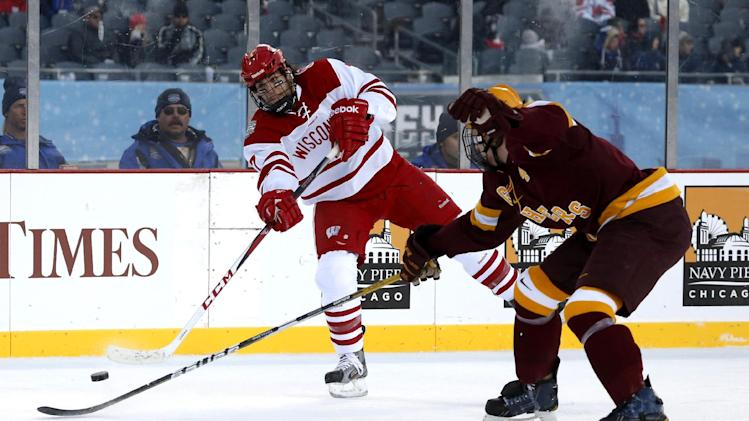 Wisconsin forward Tyler Barnes, left, shoots past Minnesota defenseman Seth Helgeson during the first period of a college hockey game at Chicago's Soldier Field, Sunday, Feb. 17, 2013. (AP Photo/Charles Rex Arbogast)