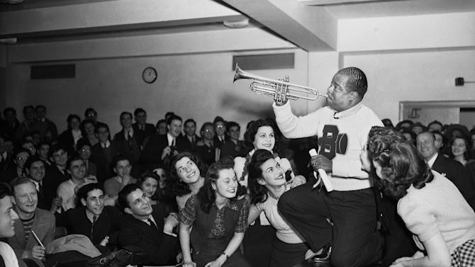 "FILE - In this March 12, 1941, file photo, Louis Armstrong, wearing a Brooklyn College sweater, performs on the campus in New York as the school honored him with the degree ""Doctor of Swing."" Armstrong, a lifelong fan and defender of the drug he called ""gage,"" was arrested in California in 1930 and given a six-month suspended sentence for pot possession. ""It relaxes you, makes you forget all the bad things that happen to a Negro,"" he once said. In the 1950s, he urged legalization in a letter to President Eisenhower. On the occasion of  ""Legalization Day,"" Thursday, Dec. 6, 2012, when Washington's new law takes effect, AP takes a look back at the cultural and legal status of the ""evil weed"" in American history. (AP Photo/File)"
