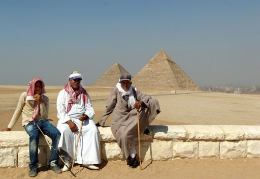 <p>Souvenir salesmen and camel owners sit waiting for visiting tourists at the historical Pyramids at Giza, south of Cairo on June 12, 2012. Egypt has signed an accord with the Saudi-based Islamic Development Bank for $1 billion in funding for the purchase of energy and food products.</p>