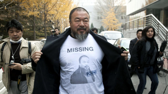 FILE - In this Nov. 16, 2011 file photo, Chinese dissident artist Ai Weiwei opens his jacket to reveal a shirt bearing his portrait as he walks into the Beijing Local Taxation Bureau in Beijing. Ai said Wednesday, May 9, 2012, a court in Beijing has accepted a lawsuit filed by his design firm, Beijing Fake Cultural Development Ltd., against the No. 2 Inspection Squad of the Beijing tax bureau for levying a $2.4 million bill on his company.  (AP Photo/Andy Wong, File)