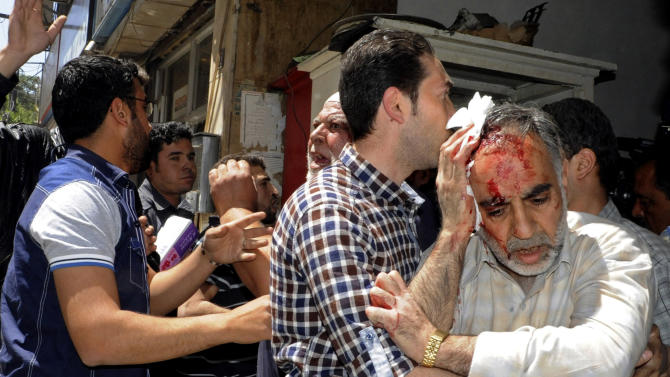 In this photo released by the Syrian official news agency SANA, a Syrian man who was injured in a powerful explosion, leaves a damaged building, in the central district of Marjeh, in Damascus, Syria, Tuesday April 30, 2013. A powerful explosion rocked Damascus on Tuesday, causing scores of casualties, a day after the country's prime minister narrowly escaped an assassination attempt in the heart of the heavily protected capital. (AP Photo/SANA)