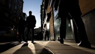 Office workers walk on the street in London. Britain was back in recession after its economy shrank in the first quarter while Prime Minister David Cameron said the country was being buffetted by the European downturn