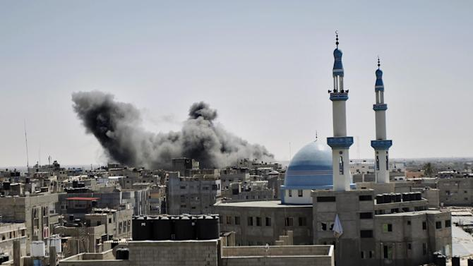 Smoke billows from a building hit by an Israeli air strike in the town of Rafah, in the southern Gaza Strip, on July 14, 2014