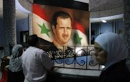 A poster of Syrian President Bashar al-Assad hangs from a wall at a hospital in Damascus. Deadly clashes broke out between deserters and Syrian government forces on Saturday as a veteran Norwegian peacekeeper headed to Damascus to take charge of a UN mission overseeing a troubled truce