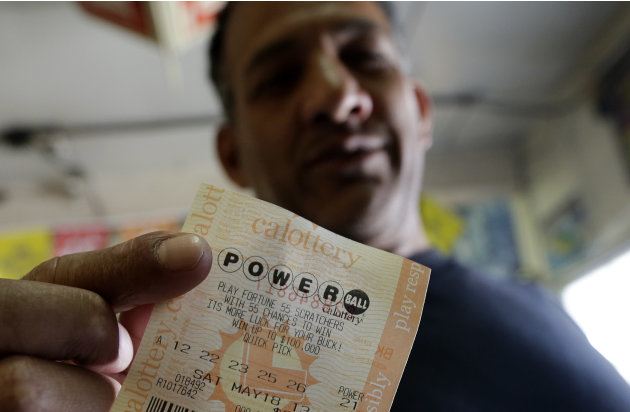 Joe Fajardo poses holding his Powerball lottery ticket after buying it at a store Saturday, May 18, 2013, in the Barrio Logan neighborhood of San Diego. With the majority of possible combinations of P