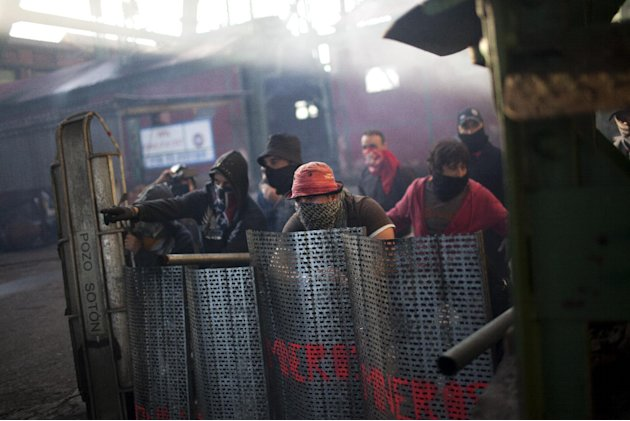 "Coal miners are seen behind their shields as they defend their position from riot police officers near the mine ""El Soton"" during clashes in El Entrego near Oviedo, Spain, Friday, June 15, 2012. Strik"