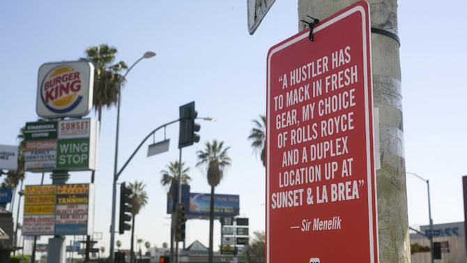 In this photo taken Friday, Feb. 21, 2014 a hip-hop themed banner is placed at the intersection of Sunset Blvd. and La Brea Ave., in Los Angeles. Street artist Jay Shells installed the sign after one day when he caught the name of a nearby intersection cited in a hip-hop song he'd been playing. Shells has put up scores of carefully drawn, hand-screened signs featuring the words of other rappers. (AP Photo/Damian Dovarganes)