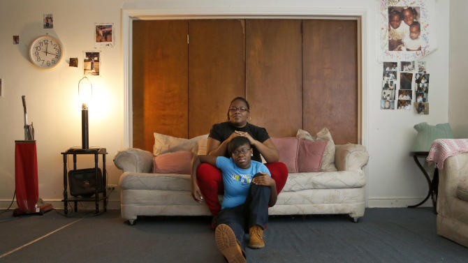 """In this Wednesday, Dec. 26, 2012 photo, Bobby McComb sits on the sofa with her 14 year-old daughter, Cerria, at their home in the Auburn-Gresham neighborhood of Chicago's South Side. In the wrong place at the right time, Cerria and a friend were wounded when gunfire aimed at a reputed gang member struck them, with a bullet exploding in Cerria's right leg. """"I'm angry,"""" Mrs. McComb says. """"I'm frustrated. I'm tired of them shooting our kids, killing our kids, thinking they can get away with it."""" (AP Photo/Charles Rex Arbogast)"""