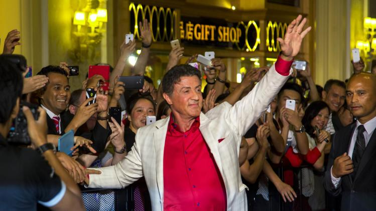 """Stallone waves to fans as he arrives on the red carpet for the special screening of """"The Expendables 3"""" in Macau"""