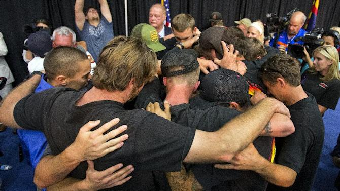 Firefighters gather in an embrace to a standing ovation during a memorial service for 19 firefighters of the Granite Mountain Hotshot Crew that were killed battling a wildfire, Monday, July 1, 2013 in Prescott, Ariz. (AP Photo/The Arizona Republic, Tom Tingle)