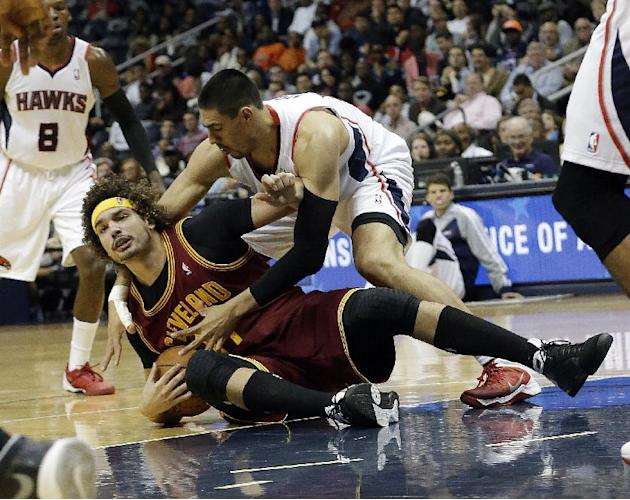 Cleveland Cavaliers center Anderson Varejao, left, and Atlanta Hawks forward Gustavo Ayon scramble for a loose ball in the second half of an NBA basketball game Friday, Dec. 6, 2013, in Atlanta
