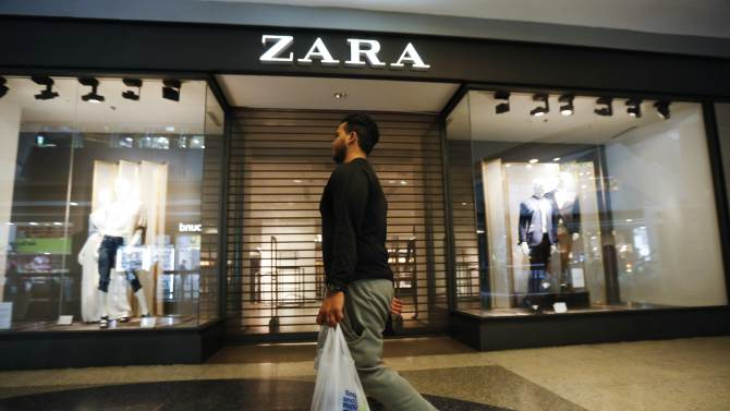 A man walks past a Zara retail store, with its shutters drawn, at a mall in Caracas