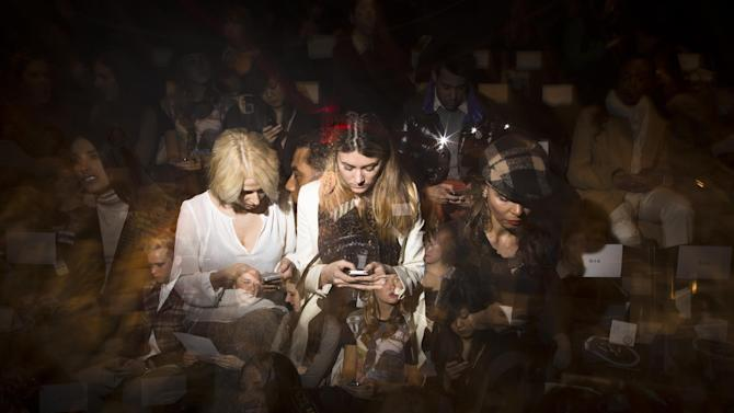In this photo made with multiple flash exposures, spectators check their mobile devices while they wait for a show to begin at the Mercedes-Benz Fashion Week tents at Lincoln Center, Thursday, Feb. 7, 2013, in New York. (AP Photo/John Minchillo)