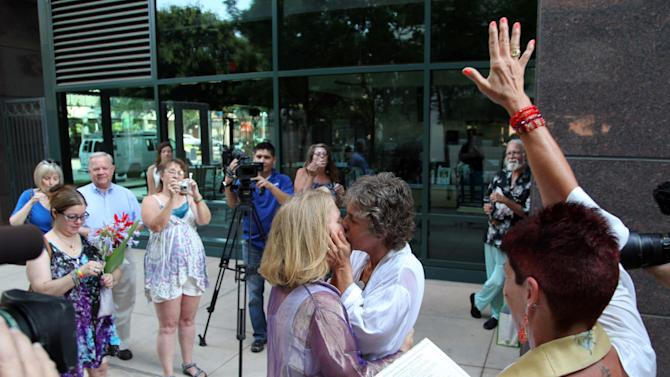 Naomi Hendrix, right, and Rio Waller kiss right after taking their wedding vows and being pronounced married in a small garden across from the Fresno County Clerk's office on Monday, June 1, 2013 . The women, who have been together for 16 years, got engaged on Wednesday, the day the Supreme Court struck down the Defense of Marriage Act. (AP Photo/Gosia Wozniacka)