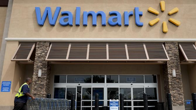 FILE - In this May 9, 2013 file photo, a worker pushes shopping carts in front of a Walmart store in La Habra, Calif. Wal-Mart Stores Inc. is expected to report quarterly results on Thursday, May 15, 2014. (AP Photo/Jae C. Hong, File)