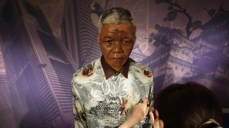 A staff member at the Madame Tussauds Tokyo wax museum adjusts the statute of Mandela in Tokyo